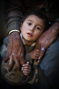 A young boy in the arns of his grandfather in Ladakh, India
