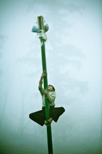 A young boy climbs a bamboo pole towards his prize during Tet. Sapa, Vietnam.